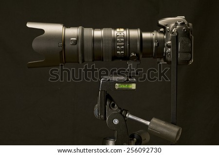 Professional Digital Camera And Zoom Lens On Tripod - stock photo