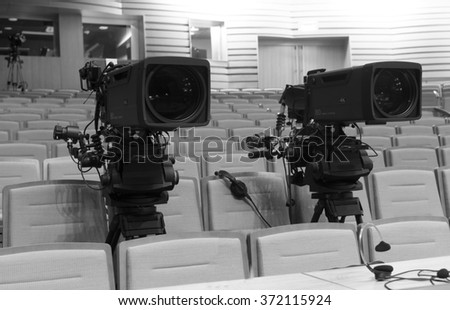 Professional digital video camera. accessories for 4k video cameras. tv camera in a concert hall.  black and white photo