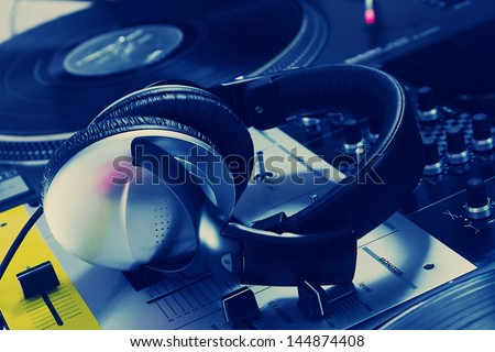 Professional dj headphones lying on sound mixing controller. Turntables record players are shown on the background. Setup is classic for a hip-hop scratch DJ. - stock photo