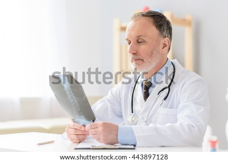 Professional doctor holding radiogram