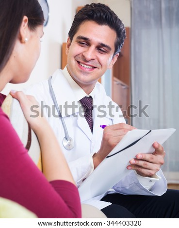 Professional doctor paying female patient a visit for checkup   - stock photo