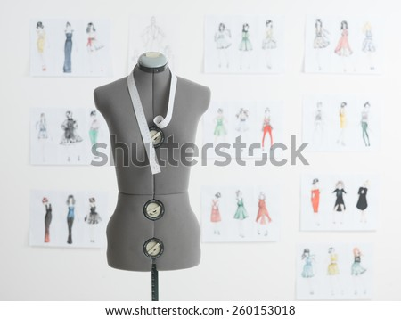 professional dressmakers dummy with measuring tape, with fashion sketches on wall behind - stock photo