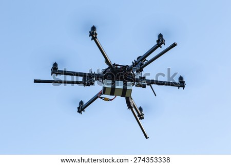 Professional drone flying on blue sky - stock photo