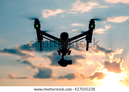 Professional drone with green lights flying at the sunset with dark clouds - stock photo