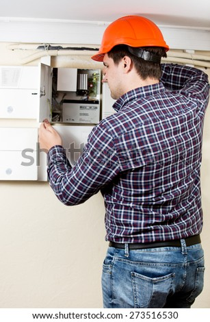 Professional electrician installing components in electrical shield - stock photo