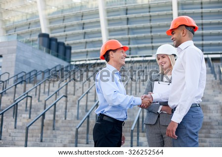 Professional engineers are shaking hands and smiling. The men are standing near building and looking at each other with trust. The woman is holding documents. Copy space in left side