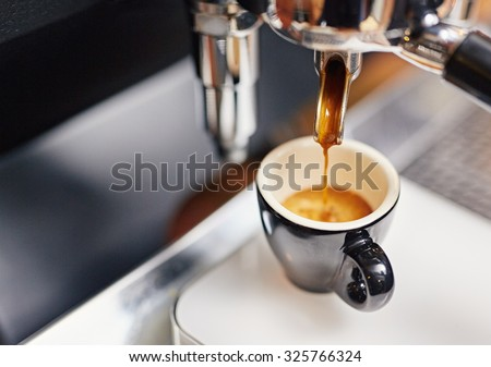 Professional espresso machine pouring strong looking fresh coffee into a neat ceramic cup - stock photo