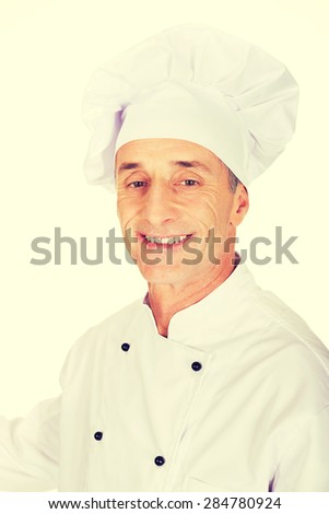 Professional experienced chef in white uniform and hat. - stock photo