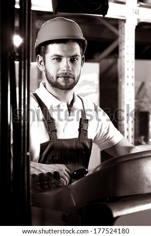 Professional factory worker sitting on forklift and working - stock photo