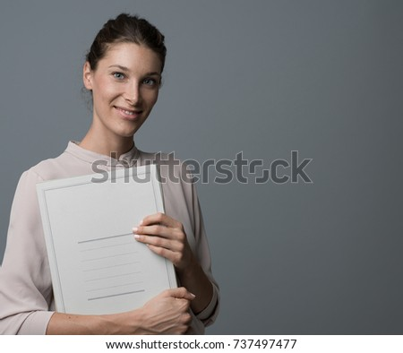 Professional female businesswoman holding paperwork and smiling at camera