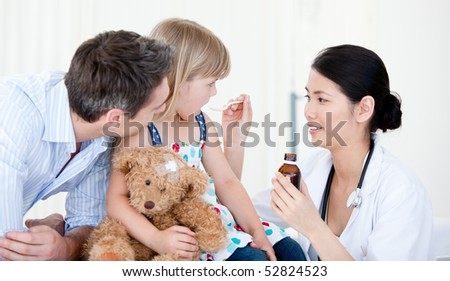 Professional female doctor giving syrup to a little girl against white background - stock photo