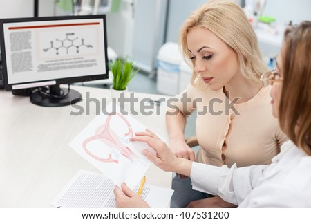 Professional female doctor is consulting blond lady - stock photo