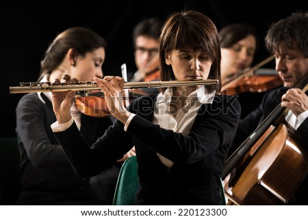 Professional female flutist in concert with symphony orchestra players on background. - stock photo