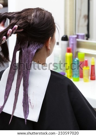 Professional female hairdresser applying color to female customer at design hair salon, woman having her hair dyed, Hair dye colouring in process
