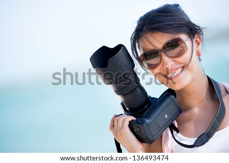 Professional female photographer holding a camera and smiling