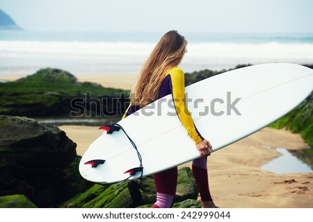 Professional female surfer walking to the ocean waves holding her surfboard, female surfer holding copy-space surfboard - stock photo