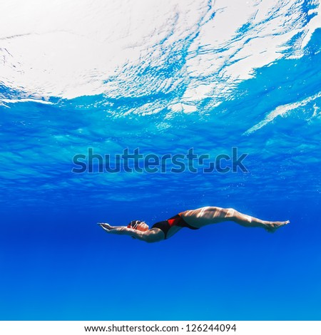 professional female swimmer moving on her back underwater in blue - stock photo