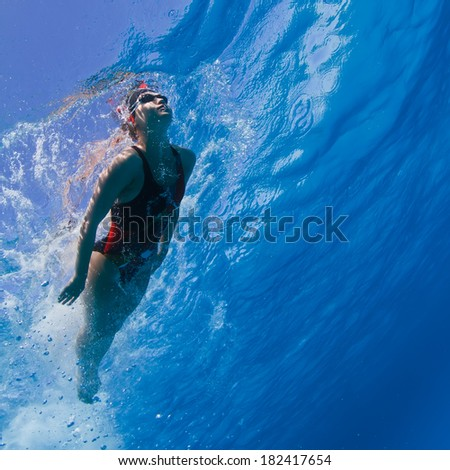 Professional female swimming in blue with air bubbles under water surface - stock photo