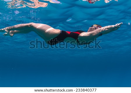 Professional female swimming underwater in blue sea with mirror on water surface and caustic effect on her skin