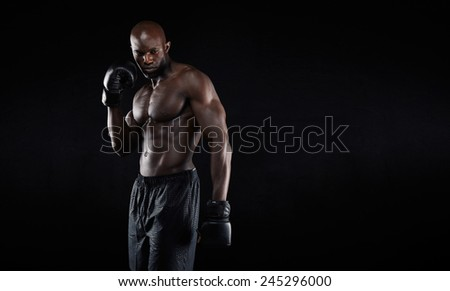 Professional fighter portrait on black background. Shirtless muscular african boxer looking at copyspace. - stock photo
