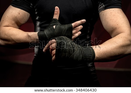 professional fighter preparing for training, wrapping his hands and wrists - stock photo