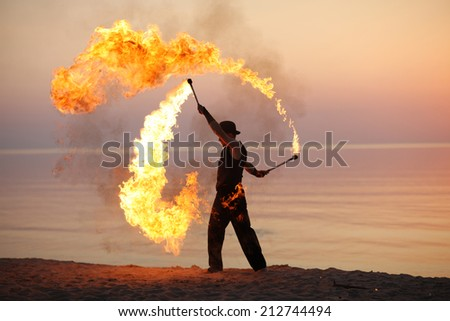 Professional fire juggler performing on the beach - stock photo