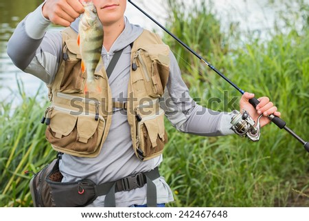 Professional fisherman on the river bank. Fisherman caught a perch and holds it in his hand. Spinning reel, fishing. Fisherman in fishing gear, fishing vest. - stock photo
