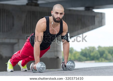 Professional fitness athlete trainer. Muscular male sportsman is training himself. Man is doing pushups. Outdoors fitness sport concept. Street workout - stock photo