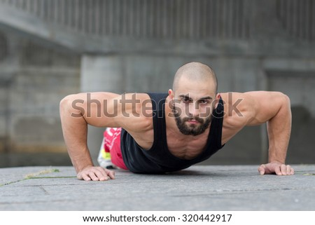 Professional fitness athlete trainer. Muscular male sportsman is training himself. Man is doing pushups. Outdoors fitness sport concept. Street workout