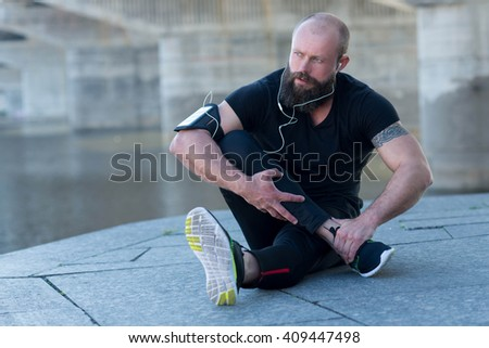 Professional fitness athlete trainer. Muscular male sportsman is training himself. Outdoors fitness sport concept. Intensive street stretching workout - stock photo