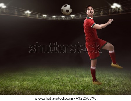 Professional football player header ball with his head - stock photo