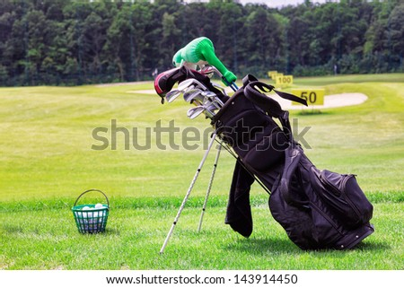 Professional golf equipment  in a golf cart and bucketful of balls on the golf course - stock photo