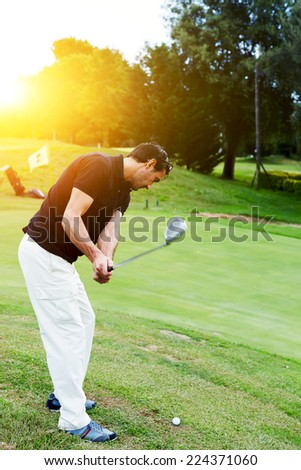 Professional golf player in action hitting golf ball at beautiful sunny evening, holidays leisure of wealthy man - stock photo