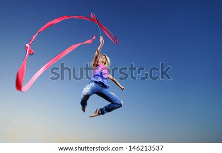 Professional gymnast woman dancer jumping with ribbon