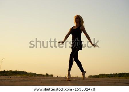 Professional gymnast woman dancer posing on concrete road - stock photo