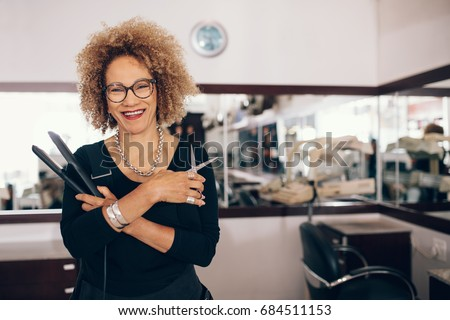 professional hair stylist holding a hair straightener and scissors woman hairdresser in happy mood at - Professional Hair Stylist