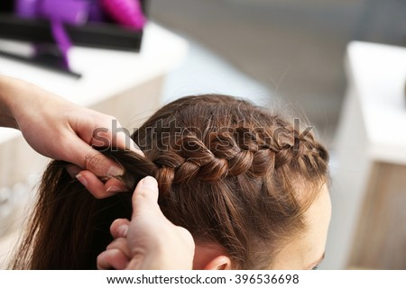 Professional hairdresser braiding clients hair