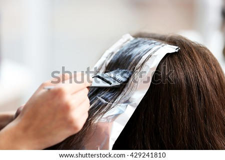 Professional hairdresser coloring hair