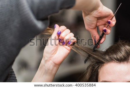 professional hairdresser does a hairstyle to the client in the beauty salon