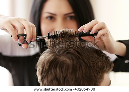 Professional hairdresser making stylish haircut - stock photo