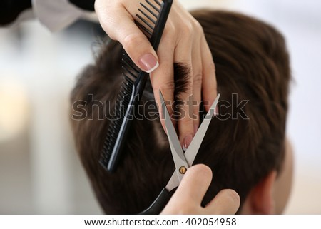 Professional hairdresser making stylish haircut, closeup
