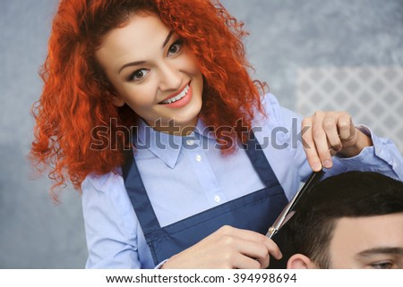Professional hairdresser making stylish man haircut - stock photo