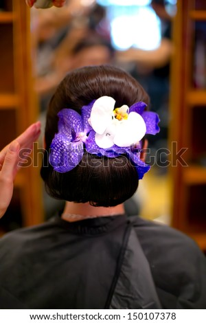 professional Hairdresser preparing a woman model and fixing a flower in hair for fashion event or wedding - stock photo