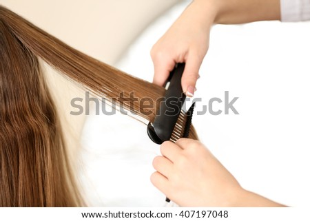 Professional hairdresser straightening hair