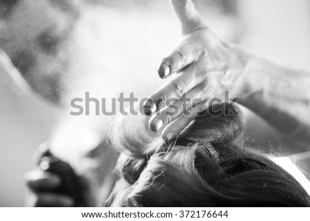 Professional hairdresser styling with hairspray long woman curly hair. Emotional detail of the hands making hot styling at hair salon. Black and white photography. Blurred background. - stock photo