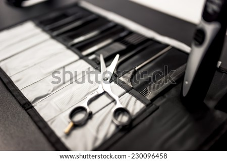 professional hairdresser tools on table with close-up of scissors and black combs set - stock photo