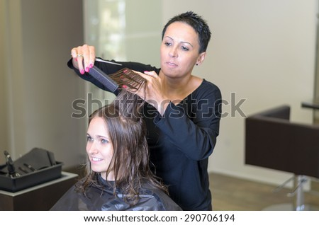 Professional hairdresser trimming the long brown hair of a young woman in her hairdressing salon snipping the ends with a pair of scissors in a hair care and beauty concept - stock photo