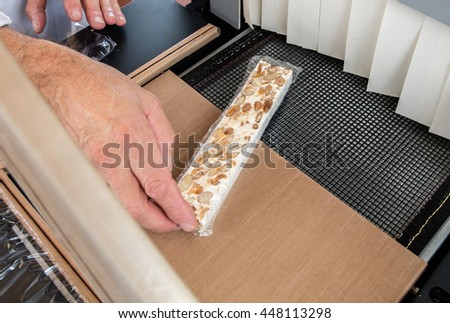 professional hands preparing hand-made French almond and honey nougat bar to pack under cellophane for commercial use