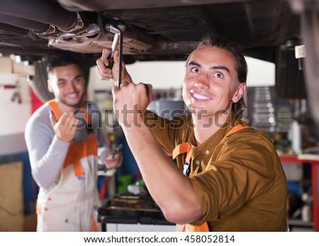 Professional happy mechanics repairing car of client - stock photo