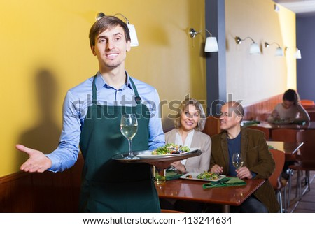 Professional happy waiter with tray posing at table of senior customers - stock photo
